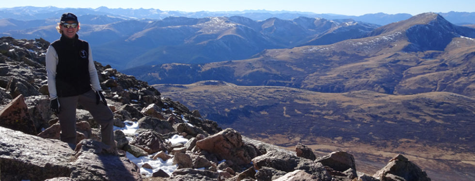 Kathleen Bober banner hiking on Mt. Bierstadt